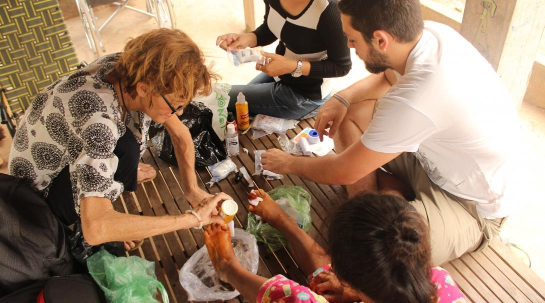 A Cambodian woman has her foot treated by Projects Abroad Medicine interns at an outreach.